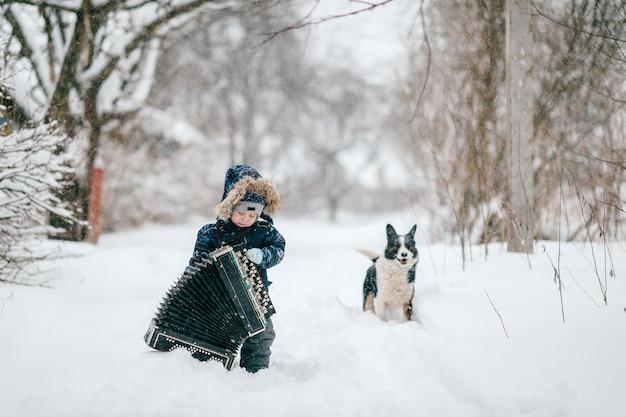 Joven músico feliz. chico cómico con gran acordeón pesado. niño masculino divertido encantador que lleva el instrumento del músico en el camino nevado del invierno al aire libre.
