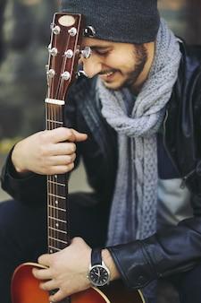 Joven músico con guitarra en la ciudad