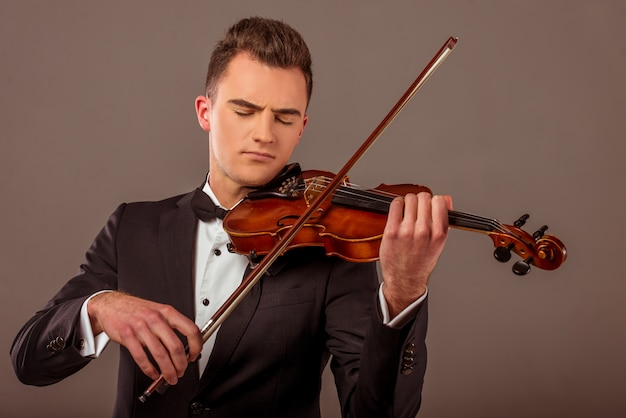 El joven músico hombre tocando el violín.