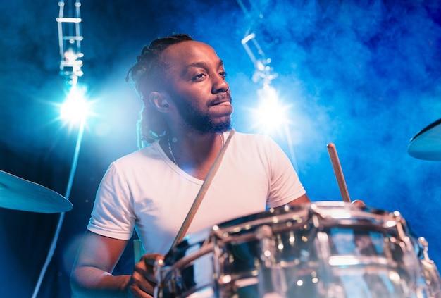 Joven músico de jazz afroamericano o baterista tocando la batería sobre fondo azul en humo brillante a su alrededor.