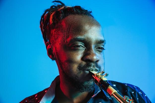 Joven músico de jazz afroamericano tocando el saxofón