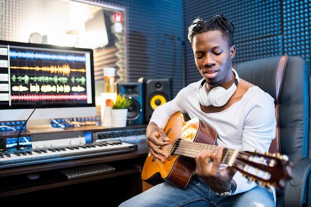 Joven músico o guitarrista contemporáneo en ropa casual tocando la guitarra mientras está sentado en el estudio de grabación de sonido