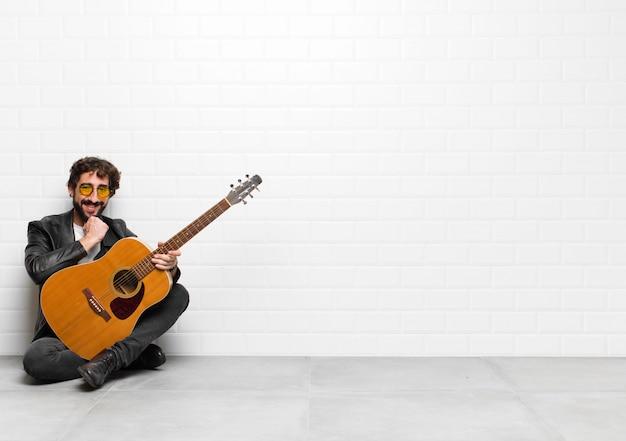 Joven músico sonriendo, disfrutando de la vida, sintiéndose feliz, amable, satisfecho y despreocupado con la mano en la barbilla con una guitarra