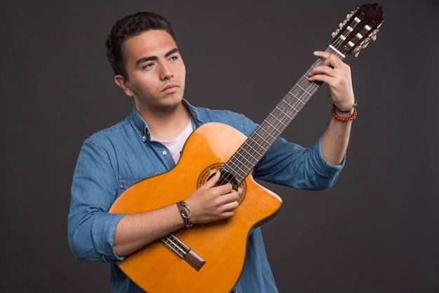 Joven músico sosteniendo una hermosa guitarra sobre fondo negro. foto de alta calidad