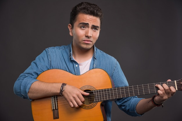 Joven músico tocando la guitarra sobre fondo negro