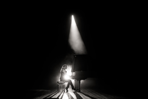 Joven músico tocando el piano de cola en el escenario