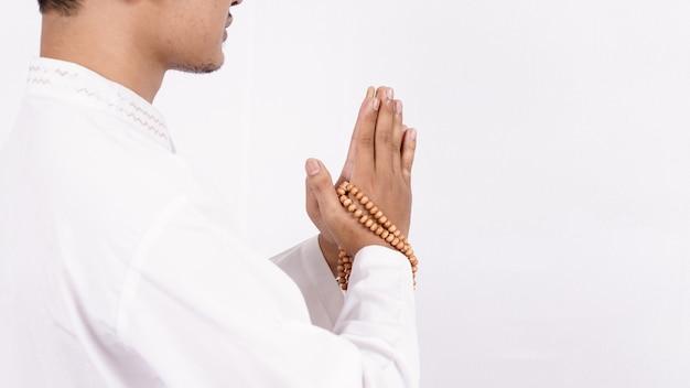 Joven musulmán asiático con gesto de bienvenida y saludo en ramadán