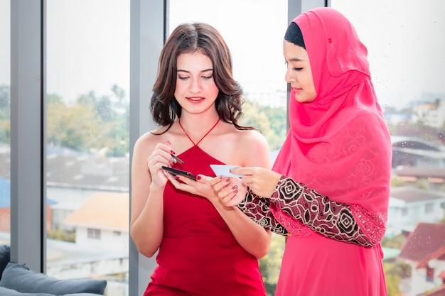 Joven musulmana y amistades caucásicas con teléfono y tarjeta de crédito disfrutando de compras