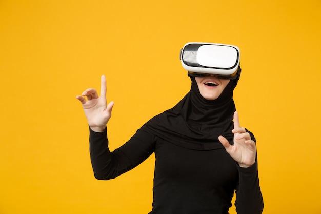 Joven musulmana árabe en ropa negra hijab mirando en auriculares de realidad virtual vr aislado en retrato de pared amarilla. concepto de estilo de vida religioso de la gente.
