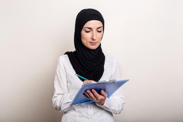 Joven musulmana con una camisa blanca y un hijab sostiene un portapapeles y toma notas