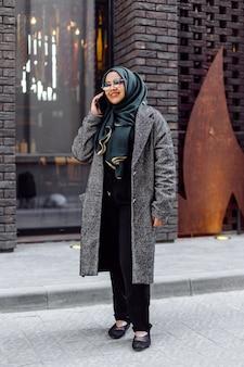 Joven musulmana hablando por teléfono