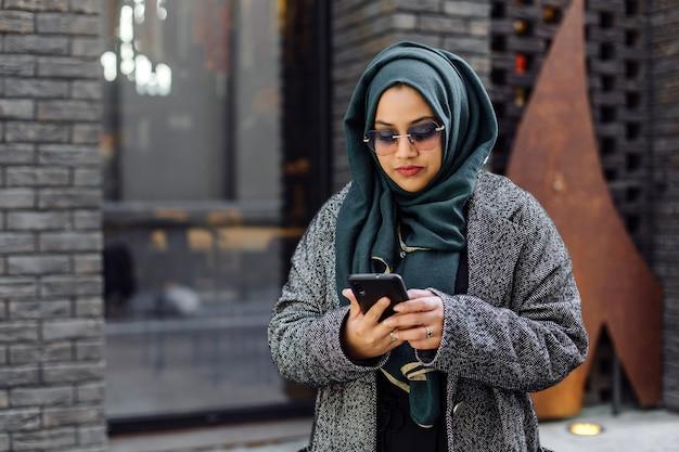 Joven musulmana mirando en un teléfono inteligente