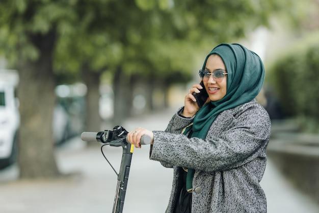 Joven musulmana montando un scooter en una calle