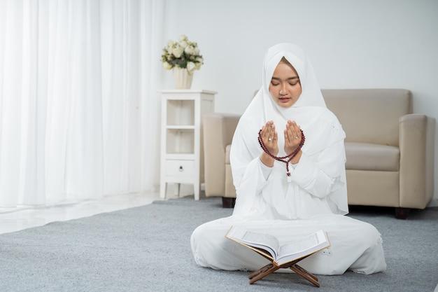 Joven musulmana rezando en ropa blanca tradicional