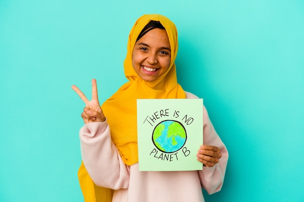 Joven musulmana sosteniendo un cartel de no hay planeta b aislado en la pared azul que muestra el número dos con los dedos.