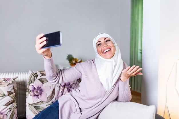 Joven musulmana con videollamada a través del teléfono móvil inteligente en casa.