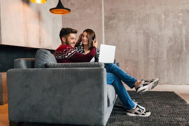 Joven muy feliz sonriente hombre y mujer sentados en casa en invierno, mirando en la computadora portátil, escuchando auriculares, estudiantes que estudian en línea, pareja en el tiempo libre juntos