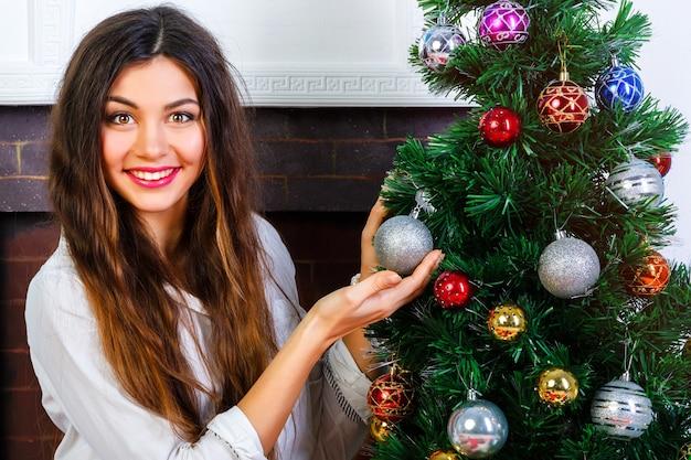 Joven muy sonriente con maquillaje brillante y cabellos largos morenas increíbles decora el árbol de navidad.