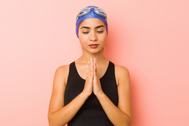 Joven nadador árabe mujer tomados de las manos en rezar cerca de la boca