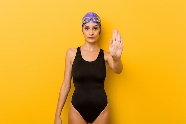 Joven nadador mujer caucásica de pie con la mano extendida que muestra la señal de stop, impidiéndole.