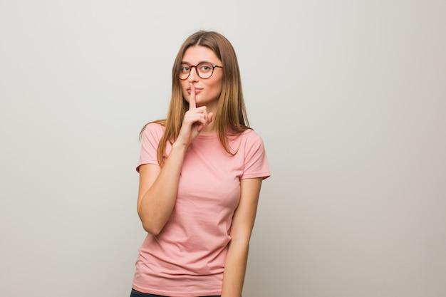 Joven natural rusa guardando un secreto o pidiendo silencio