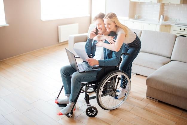 Joven con necesidades especiales. sentado en una silla de ruedas y hablando por teléfono. joven mujer abrazarlo. de pie por detrás. portátil sobre rodillas.