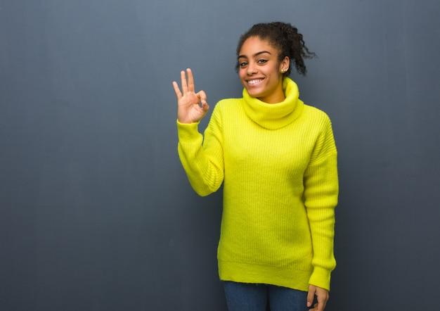 Joven negra alegre y confiada haciendo gesto bien