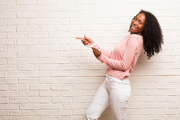 Joven negra apuntando hacia un lado, sonriendo sorprendida presentando algo, natural e informal.