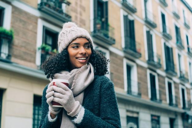 Joven negra bebiendo café vagando por las calles de madrid en invierno
