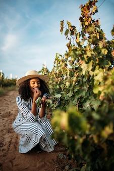 Joven negra comiendo una uva en un viñedo