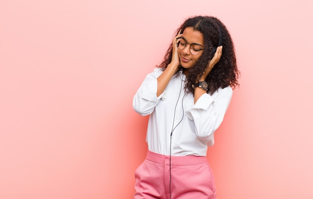 Joven negra escuchando música con auriculares en la pared rosa