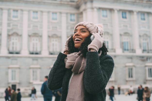 Joven negra escuchando música y bailando en el teléfono móvil cerca del palacio real en invierno