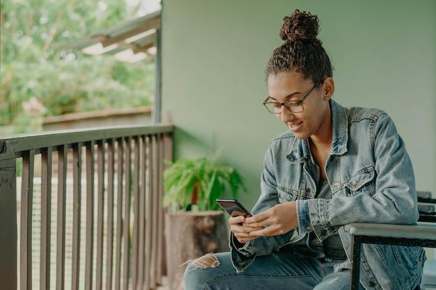 Joven negra jugando o chateando con su teléfono inteligente.