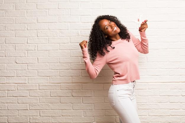Joven negra muy feliz y emocionada, levantando brazos.