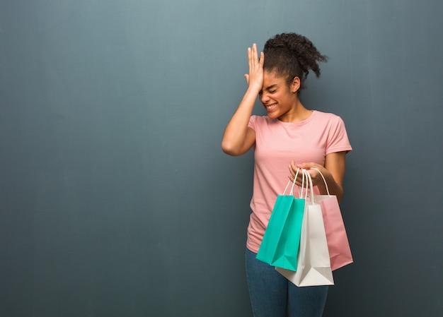 Joven negra olvidadiza, darse cuenta de algo. ella está sosteniendo una bolsa de compras.
