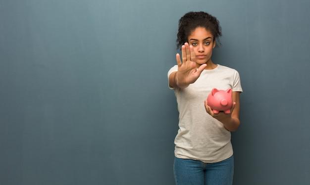 Joven negra poniendo la mano delante ella está sosteniendo una alcancía