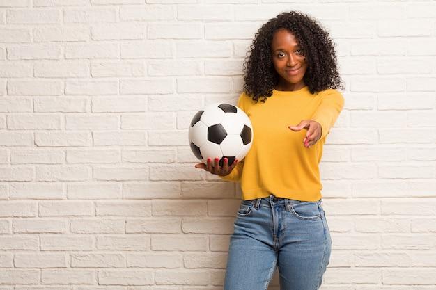 Joven negra que se acerca para saludar a alguien o gesticula para ayudar, feliz y emocionada.