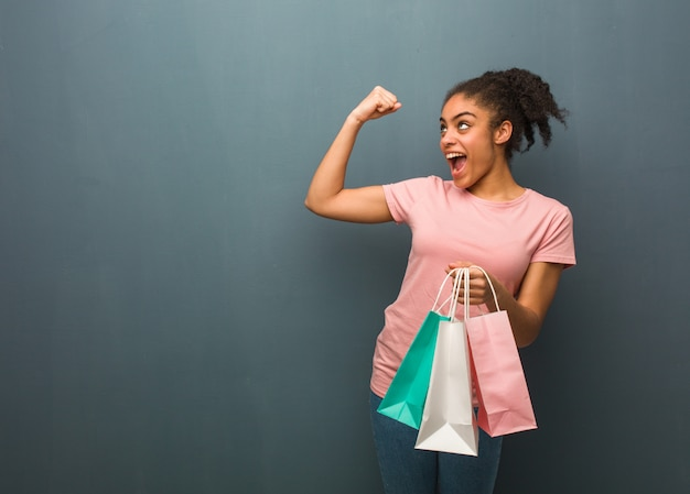 Joven negra que no se rinde. ella está sosteniendo una bolsas de compras.