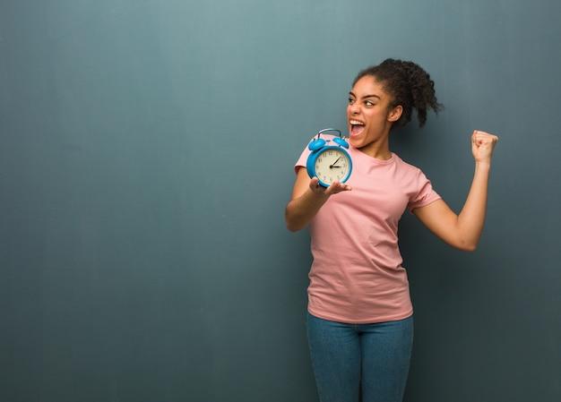 Joven negra que no se rinde. ella está sosteniendo un reloj despertador.