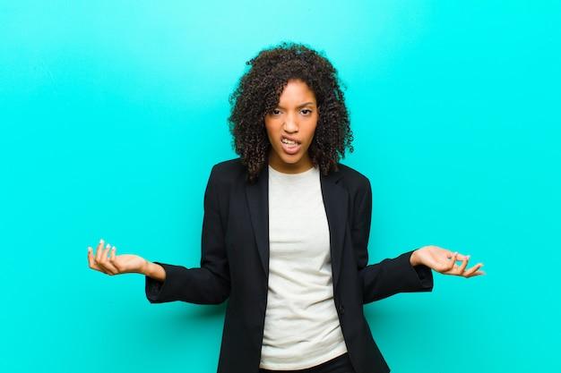 Joven negra que parece sorprendida, enojada, molesta o decepcionada, con la boca abierta y furiosa