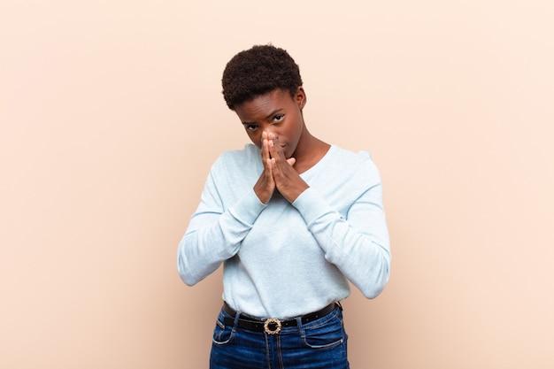Joven negra que se siente preocupada, esperanzada y religiosa, rezando fielmente con las palmas presionadas, pidiendo perdón
