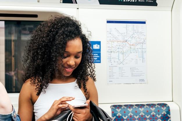 Joven negra sentada dentro del metro en el teléfono móvil