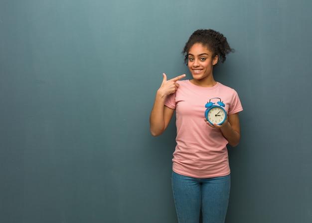 Joven negra sonríe, señalando la boca ella está sosteniendo un reloj despertador