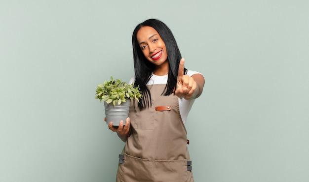 Joven negra sonriendo con orgullo y confianza haciendo la pose número uno triunfalmente, sintiéndose como una líder. concepto de jardinero