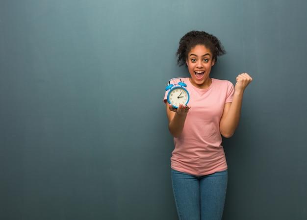 Joven negra sorprendida y conmocionada. ella está sosteniendo un reloj despertador.