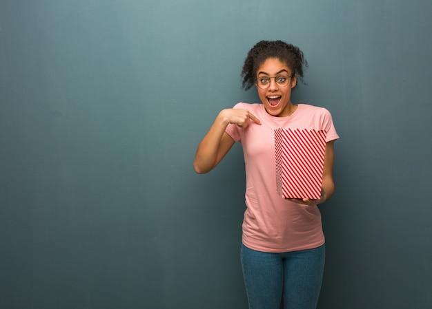 Joven negra sorprendida, se siente exitosa y próspera. ella sostiene un cubo de palomitas de maíz.