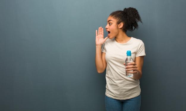 Joven negra susurrando matices de chismes. ella está sosteniendo una botella de agua.