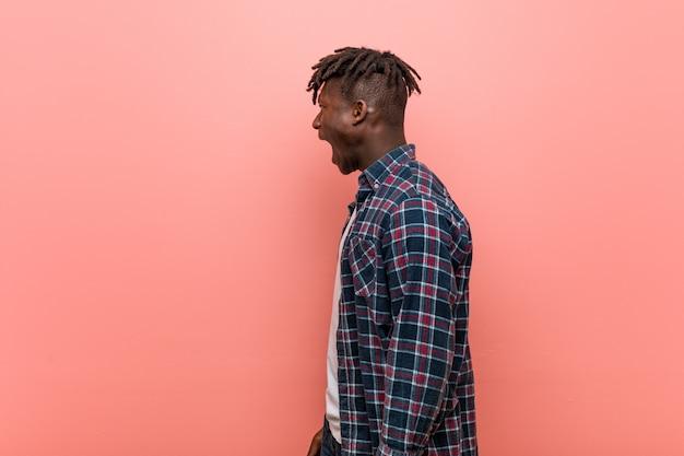 Joven negro africano gritando hacia un espacio en blanco