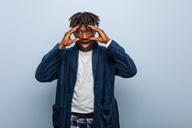 Joven negro africano vistiendo pijama manteniendo los ojos abiertos para encontrar una oportunidad de éxito.