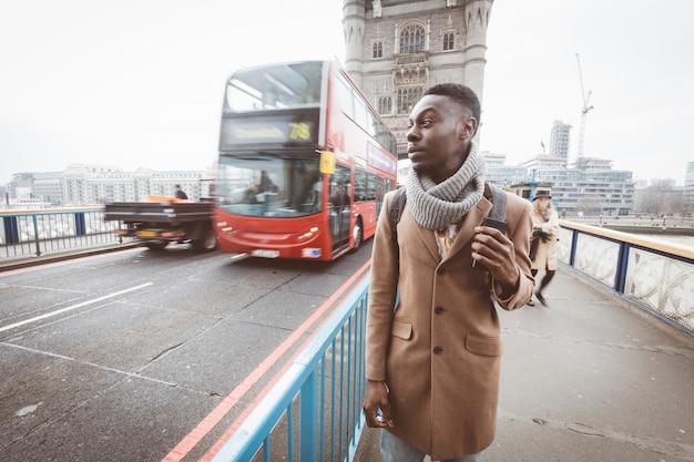 Joven negro en londres caminando en el tower bridge